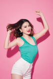 Cheerful asian girl with professional makeup and stylish hairsty. Le dancing on pink background Stock Photos