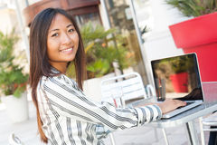 Cheerful asian girl using a laptop Stock Images