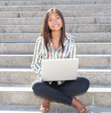 Cheerful asian girl working on laptop outdoor Royalty Free Stock Photography
