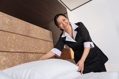 Cheerful Asian hotel maid doing the room service. Pleasant work. Cheerful delighted Asian hotel maid smiling and holding a pillow while doing the room service Stock Photos