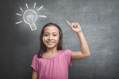 Cheerful asian kid with bright idea symbol above her head. Against blackboard background Royalty Free Stock Photography