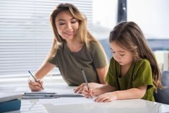 Cheerful asian kid creating art on paper. Portrait of concentrated girl drawing picture by pencil. Her mother is looking at her and smiling Stock Photography