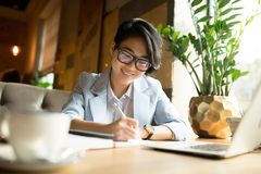 Cheerful Asian lady filling papers in cafe royalty free stock photo