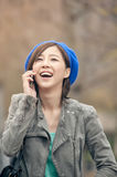 Cheerful Asian lady talking on cellphone at street in the park, Royalty Free Stock Images