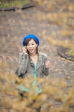 Cheerful Asian lady talking on cellphone at street in the park, Royalty Free Stock Photography