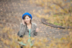 Cheerful Asian lady talking on cellphone at street in the park, Stock Image