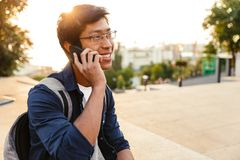 Cheerful asian male student in eyeglasses talking by smartphone. And looking away while sitting in park stock images