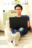 Cheerful asian man lying on the sofa Stock Images