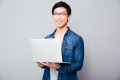 Cheerful asian man standing with laptop Royalty Free Stock Photos