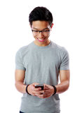 Cheerful asian man using smartphone Royalty Free Stock Photography