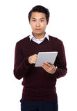 Cheerful Asian man using a tablet PC. Isolated on white background stock photography