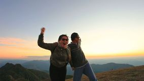 Cheerful asian man and woman relaxing on top of mountain agaisnt beautiful sunset sky stock footage