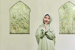 Cheerful asian muslim girl wearing hijab praying Royalty Free Stock Photos