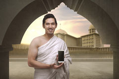 Cheerful asian muslim man with ihram clothes show mobile phone Royalty Free Stock Photo