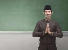 Cheerful asian muslim man wearing traditional dress with hand ge Royalty Free Stock Image