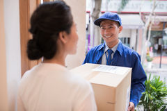 Cheerful Asian postman Royalty Free Stock Image