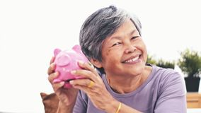 Cheerful asian senior woman shaking piggy bank smiling at camera. Portrait of mature woman saving money holding up piggy bank indo stock video