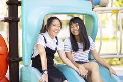 Cheerful asian teenager laughing in children playground stock images