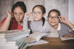 Cheerful asian teenager wearing eye glasses with school book in. Home living room royalty free stock image