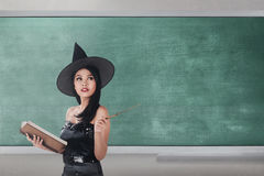 Cheerful asian wizard woman holding book and wand. Against chalkboard background Stock Photography