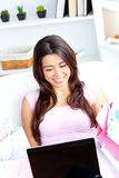 Cheerful asian woman with bags using her laptop Royalty Free Stock Photos