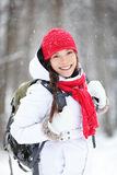 Cheerful Asian woman in falling snow. Cheerful Asian woman with a lovely broad smile standing in warm winter clothes with a satchel on her back in falling snow Stock Images