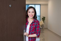 Cheerful asian woman inviting people to enter in home stock image