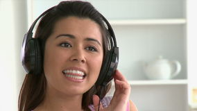 Cheerful asian woman listen to music wearing  headphones stock video footage