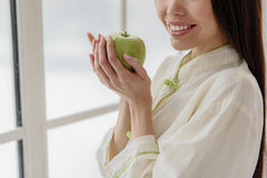 Cheerful asian woman tasting apple. Healthy food is way to be sound of body and mind. Outgoing female eat wholesome food for viable teeth. Care concept Stock Images