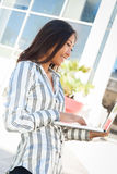 Cheerful asian woman using a laptop Stock Photo