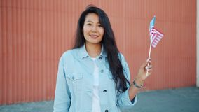 Cheerful Asian woman waving American national flag outdoors smiling. Cheerful Asian woman student is waving American national flag outdoors smiling looking at stock footage