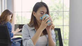 Cheerful asian young businesswoman sitting in office drinking coffee.