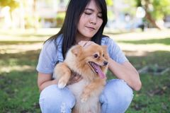 Cheerful asian young woman playing and happy fun with her dog Royalty Free Stock Photo