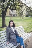 Cheerful asian young woman sitting on a bench under the blooming trees in a park. Happy asian young woman in a tweed coat and jeans sitting on a bench under the royalty free stock images