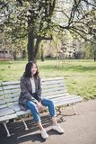 Cheerful asian young woman sitting on a bench under the blooming trees in a park. Happy asian young woman in a tweed coat and jeans sitting on a bench under the royalty free stock photography