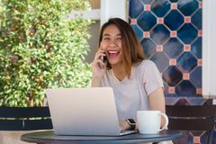 Cheerful asian young woman sitting in cafe drinking coffee and using smartphone for talking, reading and texting. Stock Photography
