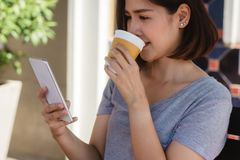 Cheerful asian young woman sitting in cafe drinking coffee and using smartphone for talking, reading and texting. royalty free stock images