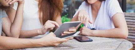 Cheerful asian young women sitting in cafe drinking coffee with friends and talking together. Attractive asian women enjoying coffee while using smartphone for royalty free stock photo