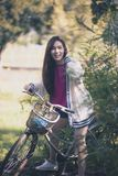 Cheerful asian younger woman riding on retro bicycle in green park royalty free stock photos