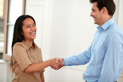 Cheerful asiatic lady giving hands greeting. Portrait of cheerful asiatic lady on brown blouse giving hands greeting to a businessman while smiling at you and Stock Photos