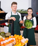 Cheerful assistants demonstrating assortment. Cheerful shopping assistants demonstrating assortment of grocery shop royalty free stock images