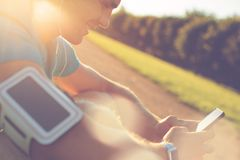 Cheerful athlete using smartphone in the park before training. Lens flares Stock Image