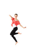 Cheerful, athletic girl jumping and looking into the camera. Isolated. Stock Photo