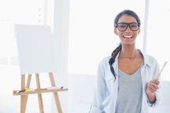 Cheerful attractive artist holding paintbrush Stock Photo