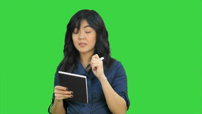 Cheerful attractive asian girl listening and writing down notes on a Green Screen, Chroma Key stock video