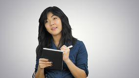 Cheerful attractive asian girl listening and writing down notes on white background. Close up. Professional shot in 4K resolution. 080. You can use it e.g. in stock image