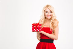Cheerful attractive blonde female in red dress holding present Stock Photography