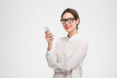 Cheerful attractive businesswoman in glasses standing and using mobile phone Stock Photo