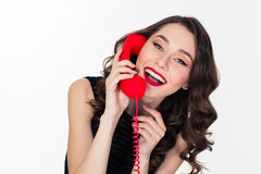 Cheerful attractive curly retro styled woman talking on red telephone Stock Image