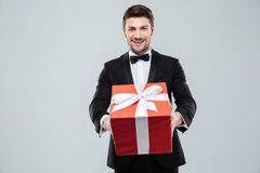 Cheerful attractive man in tuxedo giving you red gift box Royalty Free Stock Photo